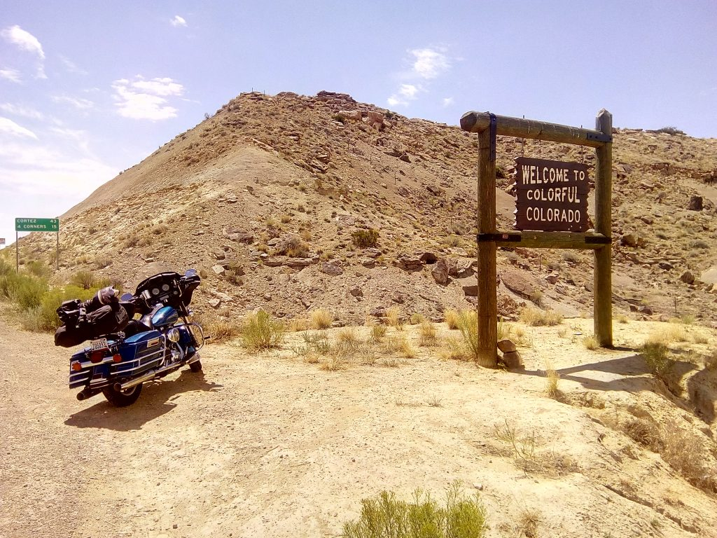 Une moto à côté d'un panneau Colorado