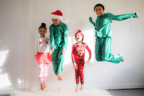 Quatre enfants en habits rouge et vert sautant de joie