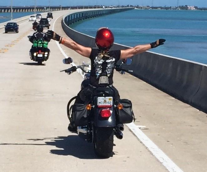 Martine, les bras levés sur sa moto